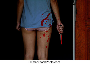 halloween concept, bloody woman holding a knife stand at the door
