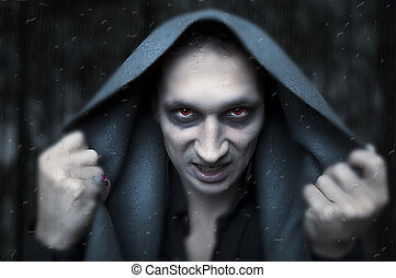 Portrait horrible fashion male vampire (demon or evil wizard) knocking to rainy and misted window. Halloween concept