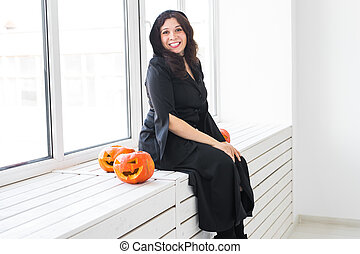 Halloween concept - Happy witch with pumpkin Jack-o'-lantern on light background