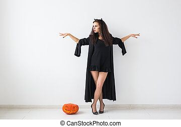 Halloween concept - Happy witch with pumpkin Jack-o'-lantern on light background with copy space