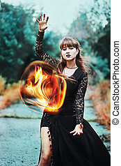 Powerful witch with fireball in hands