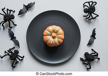 Halloween concept table setting with black spiders on grey table .Flat lay, top view. Party accessories.