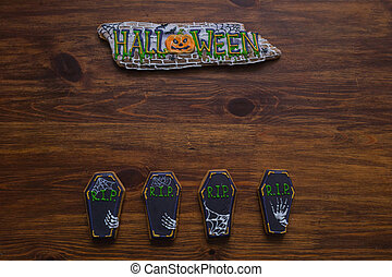 Halloween cookies in the form of coffins on a wooden table.