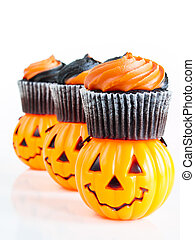 Halloween cupcakes decorated with black and orange swirled icing.