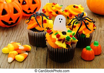 Halloween cupcakes and candy on rustic wooden table...