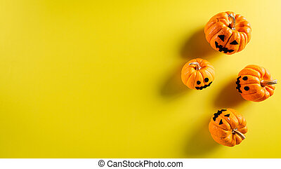 Halloween decorations made from ghost pumpkin on pastel yellow background. Flat lay, top view with copy space for text.