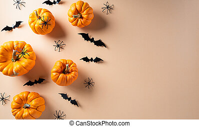 Halloween decorations made from pumpkin, paper bats and black spider on pastel orange background. Flat lay, top view with copy space for text.