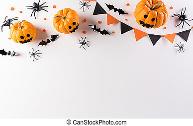 Halloween decorations made from pumpkin, paper bats and black spider on white background. Flat lay, top view with copy space for text.