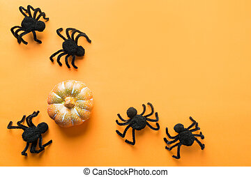 Halloween decorations with black spiders and pumpkin on orange background. Flat lay, top view, copy space.