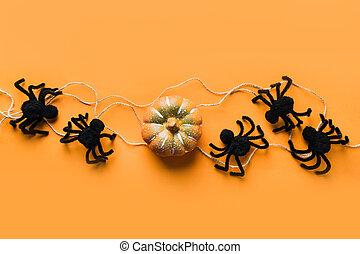 Halloween decorations with black spiders and pumpkin on orange background. Flat lay, top view