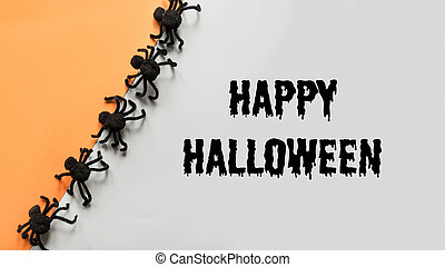 Halloween decorations with black spiders on orange and grey. Flat lay, top view, copy space.