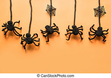 Halloween decorations with black spiders on orange background. Flat lay, top view, copy space.