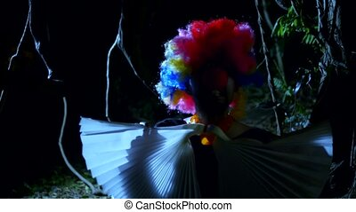 Halloween, evil clown with a bow around his neck in a...
