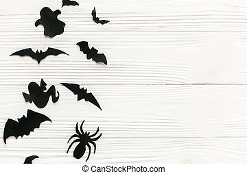 Halloween flat lay. Black paper bats, spiders, ghosts top view on white rustic wooden background. Trick or treat. Space for text. Season's greeting card mockup.