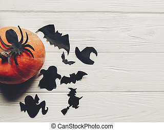 halloween flat lay. happy halloween concept. pumpkin with witch ghost bats and spider black decorations on white wooden background top view with space for text. seasonal greetings