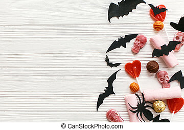 Halloween flat lay. Holiday candy with bats, spiders, ghosts, skulls top view on white rustic wooden background. Trick or treat. Halloween background. Season's greeting card mockup