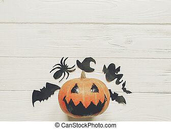 halloween flat lay. jack lantern pumpkin with witch ghost bats and spider black decorations on white wooden background top view, space for text. seasonal greetings. happy halloween concept