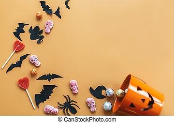 Halloween flat lay. Jack o Lantern bucket with holiday spilling candy, bats, spiders, skulls on orange paper. Space for text. Halloween background. Season's greeting card mockup