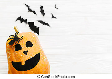 Halloween flat lay. Jack o lantern pumpkin and black bats, ghost, spider on white wooden background, copy space. Modern halloween decorations. Minimalistic flat lay