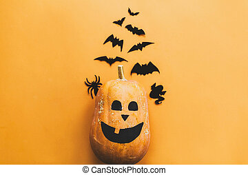 Halloween flat lay. Pumpkin jack lantern and black bats, ghost, spider paper decorations on yellow background, copy space. Trick or treat concept. Happy Halloween