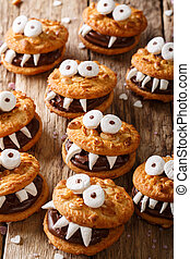 Halloween food: monsters of nutty cookies with chocolate cream close-up on the table. vertical