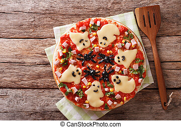 Halloween Food: Pizza with ghosts and spiders close-up....