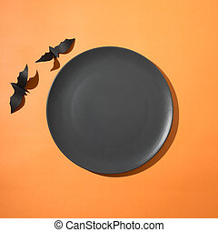 Halloween frame of two bats and plate on orange paper. Top view with space for text.