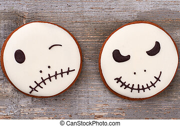 Halloween gingerbread cookies on wooden background.