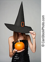 Halloween girl witch hat holding pumpkins in hand -...