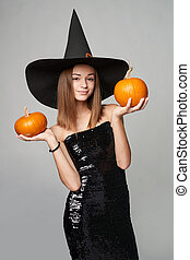 Halloween girl witch hat holding pumpkins in hand - Smiling...