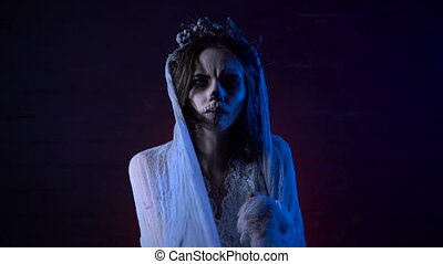 Halloween girl with scary make-up and wreath of dry flowers on head standing moving hands in veil  looking at the camera. Ghost  dead bride  sad face  in the dark room.