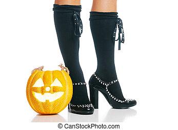 Halloween glowing pumpkin near female legs in black shoes.