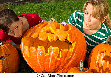Halloween grimace - Two girlfriends admire her carved...