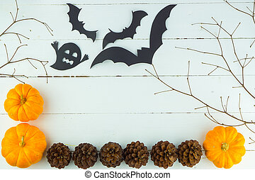 Halloween holiday background with orange pumpkin, ghost and bat on white wooden table with copy space for text. Flat lay, top view - Image