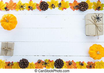 Halloween holiday background with orange pumpkin, ghost, spider and bat on white wooden table with copy space for text. Flat lay, top view