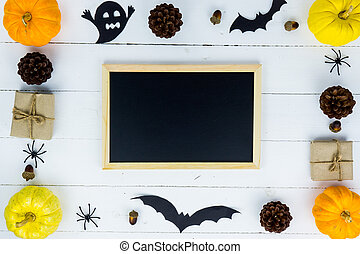 Halloween holiday background with orange pumpkin, ghost, spider, bat and black board on white wooden table with copy space for text. Flat lay, top view