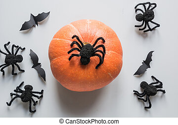 Halloween holiday background with pumpkin, black spiders, web on grey.