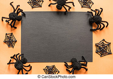 Halloween holiday blank with party decor, black spiders, web on orange. Flat lay, top view. Space for text