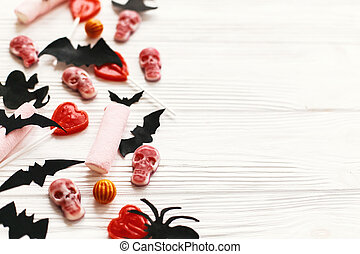 Halloween. Holiday candy with bats, spiders, ghosts, skulls top view on white rustic wooden background. Trick or treat. Halloween background. Season's greeting card mockup