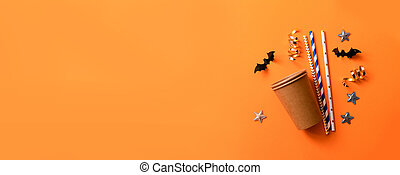 Halloween holiday decorations. Striped straws with paper bats and confetti , spiders on white background. Flat lay, top view