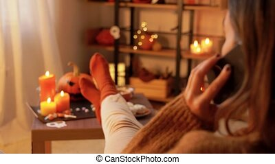 halloween, holidays and leisure concept - young woman calling on smartphone at home on halloween