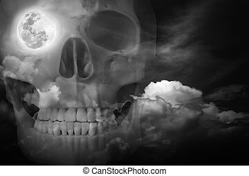 Halloween horror night background. Double exposure of human skull combined sky with clouds . Full moon on right eye socket. Black and white style. The moon taken with my own camera, no NASA images used.