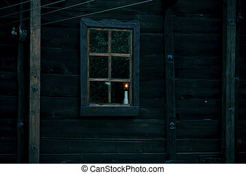 Halloween horror building. Reflection and shadows of a spooky tree in the window of an old wooden dark mystical ghostly house in the forest and the light from the lamp on the windowsill in the night darkness