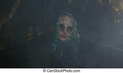Halloween horror clown sitting in darkness outside in smoke...