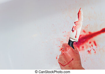 Halloween horror concept. Image of unknown woman hands holding a knife with bloody stain in the sink.