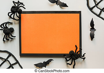 Halloween invitation with black spiders, bat on grey. Flat lay, top view, copy space.