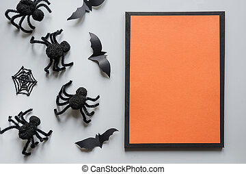 Halloween invitation with black spiders, bat on grey. Flat lay, top view, copy space. Party accessories. Happy halloween concept.