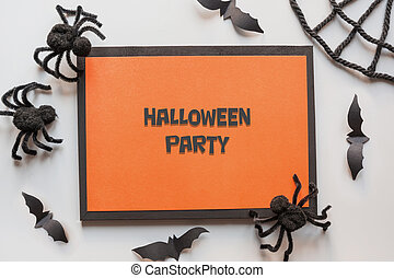 Halloween invitation with black spiders, bat on grey. Flat lay, top view, copy space. Party accessories. Happy Halloween - text.