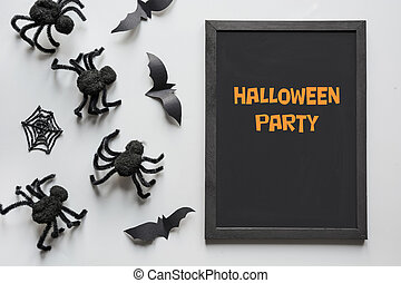 Halloween invitation with black spiders on grey. Flat lay, top view, copy space. Party accessories. Happy halloween concept.
