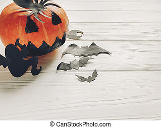 halloween. jack lantern pumpkin with witch ghost bats and spider black decorations on white wooden background top view. seasonal greetings. happy halloween concept, holiday celebration